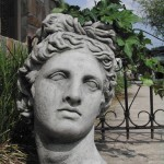 "#415 Bust of Apollo Planter (39 lbs.) 16"" H x 10 1/2"" L x 9 1/2"" W. Very classical and romantic, this weathered reproduction of the 4th century Greek sculpture Apollo Belvedere is perfect for gardens as well as interiors. Planter has planting space at top of head."