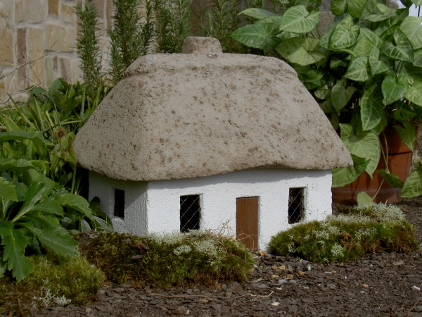 """#526 Scottish Cottage, Approx. 16"""" x 11"""" x 13"""" H (32 lbs.) The second in our Cottage Series exudes loads of old world charm and has essential details and wonderfully textured and aged surfaces. The removable roof allows a variety of uses, making this a unique, collectible piece. Comes with poem to tell its tale."""