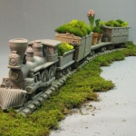 #369 Civil War Locomotive Package. Fantastic detail and craftsmanship make this garden train/planter irresistable. Includes Locomotive, Coal Car, Flat Car, Box Car and Caboose, both with Removeable Lid, and 6 Sections of Track.